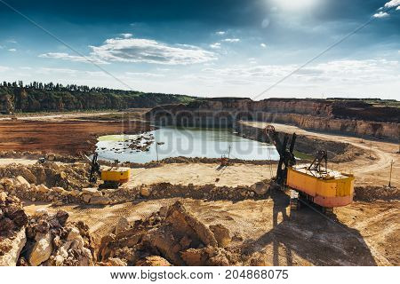 Quarry landscape and equipment with heavy duty machinery, excavators and loaders. Construction industry concept