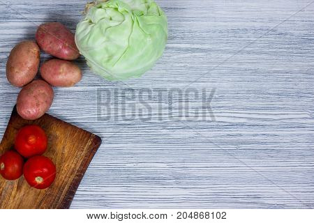 Vegetables, herbs and spices on an old wooden table, Caesar salad ingredients, top view, copy space, rustic style. Vegetarian food, health or cooking concept.