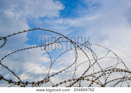 Wire and blue sky with clouds. Safety fence of barbed wire against the blue sky