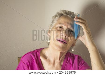 Ice pack for headache in older woman