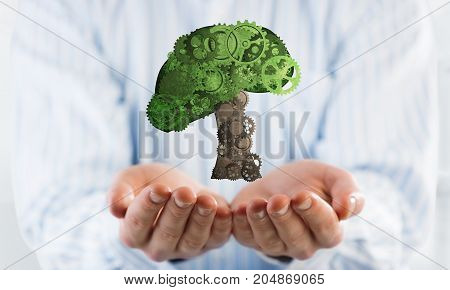 Close of male hands holding green tree made of gears mechanism