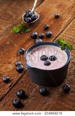 Youghurt with blueberries on a wooden table