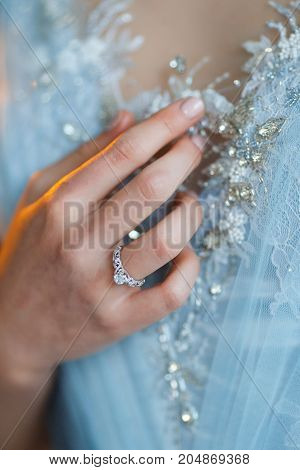 Bride hand with beautiful diamond ring on blue dress
