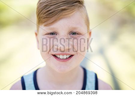 A Young beautiful redheaded boy playing outside