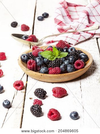 Ripe and sweet berries in bowl on wooden white table