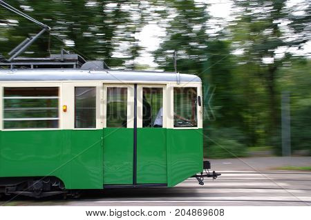 Green historic tram in motion. Old public transportation train in Poznan (Poland).