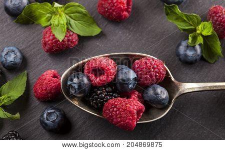 Ripe and sweet berries on vintage metal spoon on black table