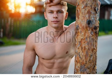Model male athlete standing in the park by the tree, resting close-up, portrait of a muscular trainer. The concept of a healthy lifestyle. In the summer sunlight. Tanned skin. Lifestyle in nature.