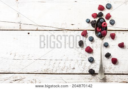 Ripe and sweet berries on vintage metal spoon on wooden white table