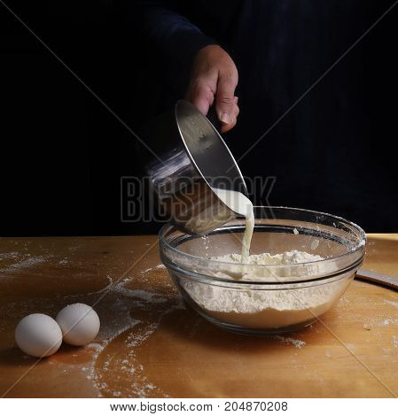 older female hand pouring milk from a pot into a bowl filled with flour on a wooden kitchen worktop preparation for baking dark background with copy space selected focus