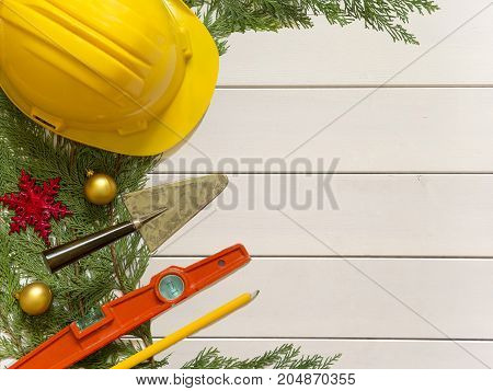 Protective Helmet, Mason Tools  And Christmas Decorations On Wooden White Background