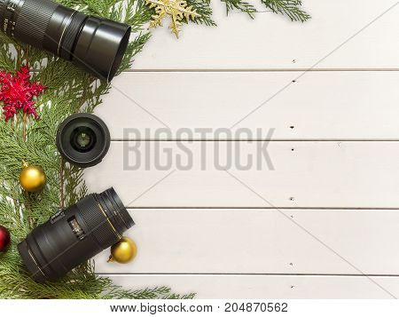 Lenses for reflex camera and Christmas decorations on a white wood background
