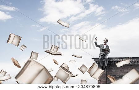 Funny man in red glasses and suit sitting on building top and reading book