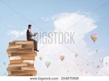 Young businessman sitting on pile of books with one in hands