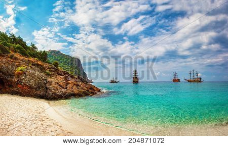 tropical sea bay with ships in sunny day. Landscape of sea rocks and beach with white sand