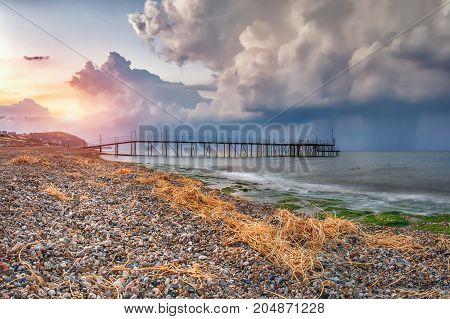 Landscape beach with sea pier at sunrise