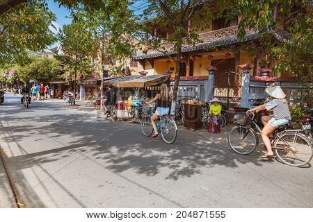 HOI AN VIETNAM - MARCH 15 2017: Group of people travel Hoian old town ancient house country heritage city friendly with environment walk bicycle or pedicab on street traveller visit at Vietnam