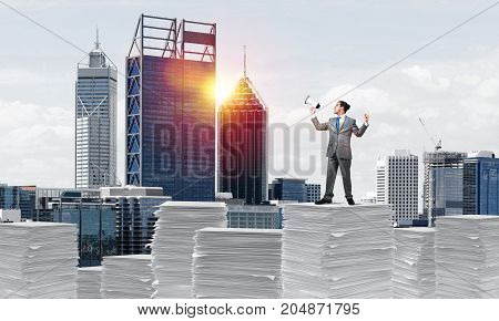 Businessman in suit standing on pile of documents with speaker in hand with cityscape on background. Mixed media.