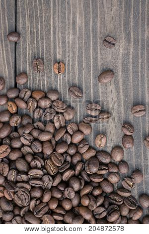 Fresh coffee beans on rustic wooden background.