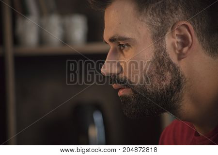 Human thought. Close up of young man face portrait with beard who sad and looking forward. Brooding emotions on face. Sadness and sorrow