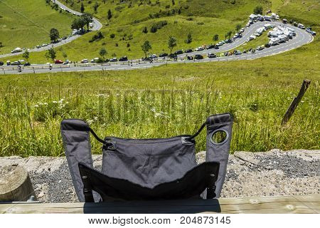 A specific folding chair for a Tour de France spectator is ready to be used with many hours before thje apparition of the cyclists. Location: Col de Peyresourde in Pyrenees Mountains.