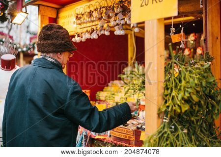 Prague, December 15, 2016: An elderly man buys Christmas presents to his grandchildren at the Christmas market. Gifts for the holiday. Celebrating Christmas.