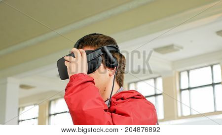 Teenager in VR headset enjoying virtual reality digital game. Virtual and augmented reality are increasingly used in human lives.