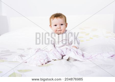 A Portrait of a crawling baby on the bed in her room