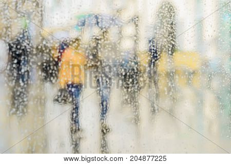 Raindrops on window glass, few unrecognizable people rush home under umbrellas, abstract blurred background. Concept of seasons, weather, modern city