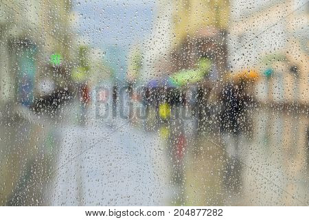 Raindrops on window glass, people walk on road in rainy day, blurred motion abstract background. View from the window on city street. Concept of shopping, modern city, walking, lifestyle