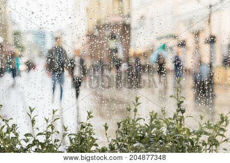Young couple walking hand in hand without an umbrella, not noticing the rain. Concept of modern city, love, lifestyle. Abstract blurred background