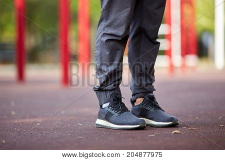 Close-up picture of man's legs in black trousers and sports sneakers on a blurred playground background. Copy space.