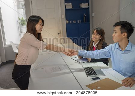 Interviewers congratulate young candidate on passing the interview excellently