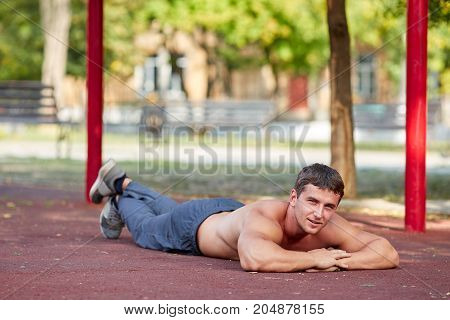 A handsome smiling man lying on the ground on a blurred stadium area background. Shirtless sports man with sexy biceps.