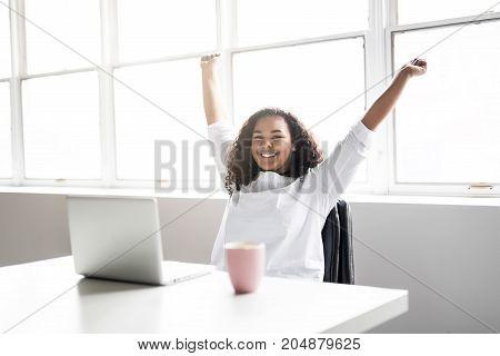 A Happy teen taking a break at desk in her office