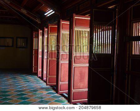 Hue, Vietnam - September 13 2017: Beautiful red wooden doors in Hue citadel, Vietnam, Asia. Famous destination for tourists. UNESCO Heritage site.