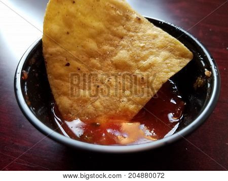 a single tortilla chip dipped in salsa cup