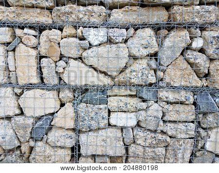 a wall made out of many rocks inside a metal cage