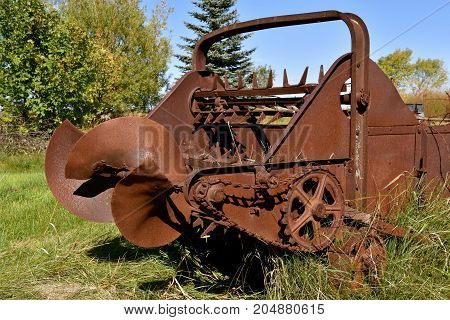 The beater and gears of an old rusty manure spreader