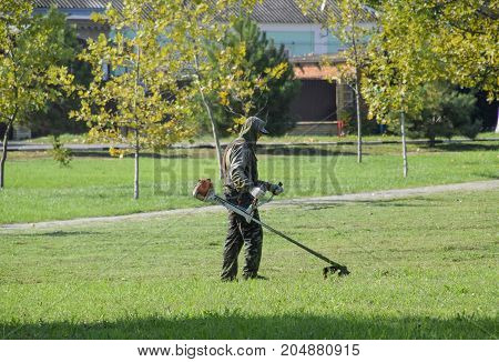 Worker Mowing Grass With A Gasoline Brush. Trimmer.