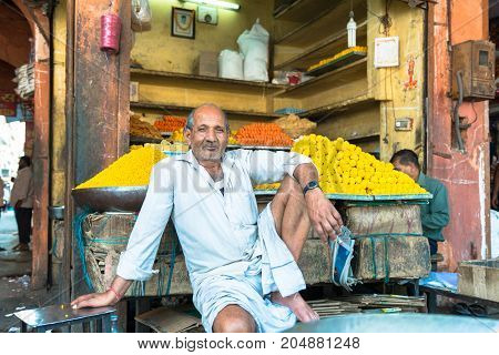 JAIPUR RAJASTHAN INDIA - MARCH 11 2016: Horizontal picture of indian man posing in front of his store in Jaipur known as pink city of Rajasthan in India.