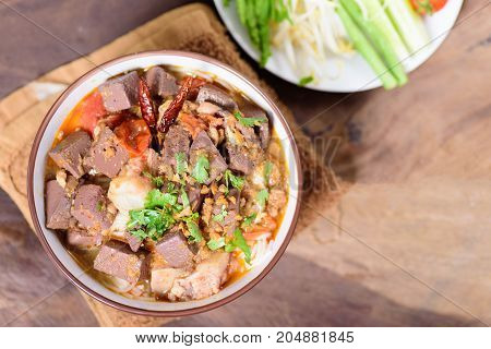 Thai Northern food (Kanom Jeen Nam Ngeaw) with vegetables on wooden background,spicy rice noodles soup,rice vermicelli served with curry