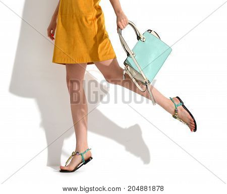 Beautiful woman legs walking running in yellow brown fashion body dress cloth with blue mint hand bag clutch on a white background