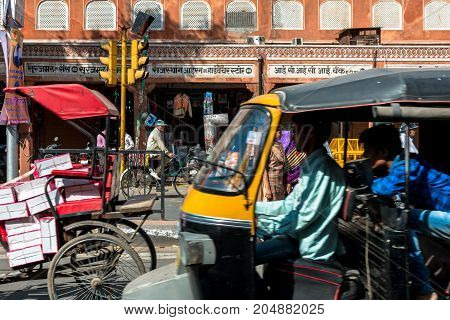JAIPUR RAJASTHAN INDIA - MARCH 11 2016: Horizontal picture of crowded streets full of rickshaw motorcycle people and tuk tuk in Jaipur known as pink city of Rajasthan in India.