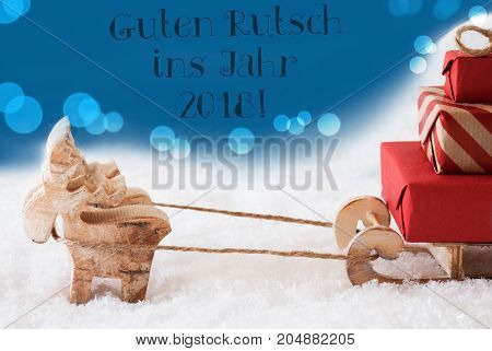 Moose Is Drawing A Sled With Red Gifts Or Presents In Snow. Christmas Card For Seasons Greetings. Blue Background With Bokeh Effect. German Text Guten Rutsch Ins Jahr 2018 Means Happy New Year