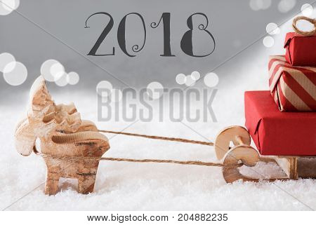Moose Is Drawing A Sled With Red Gifts Or Presents In Snow. Christmas Card For Seasons Greetings. Silver Background With Bokeh Effect. Text 2018 For Happy New Year Greetings