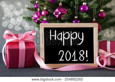 Christmas Tree With Rose Quartz Balls And Bokeh Effect. Gifts Or Presents In The Front Of Cement Background. Chalkboard With English Text Happy 2018 for Happy New Year