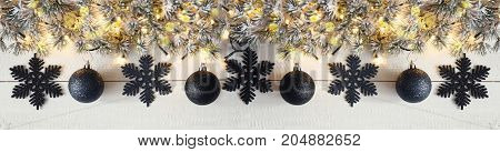 White Wooden Background With Bokeh Effect. Christmas Banner With Black Christmas Decoration Like Balls And Snowflakes. Fir Branches With Fairy Lights.