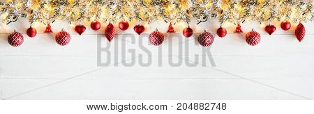 White Wooden Background With Copy Space And Bokeh Effect. Christmas Banner With Red Christmas Decoration Like Balls, Hearts And Bells. Fir Branches With Fairy Lights.
