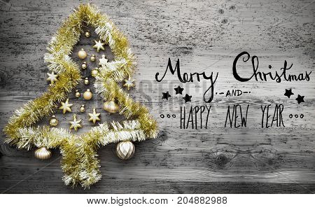 Black Calligraphy With English Text Merry Christmas And Happy New Year. Golden Tinsel Christmas Tree. Christmas Ball Ornament On Gray Wooden Background
